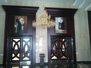 נברשת הזהב ושתי תמונות ענקיות מעל דלתות הכניסה לבית הכנסת